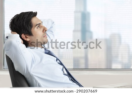 Thoughtful young business man relaxing on office chair - stock photo