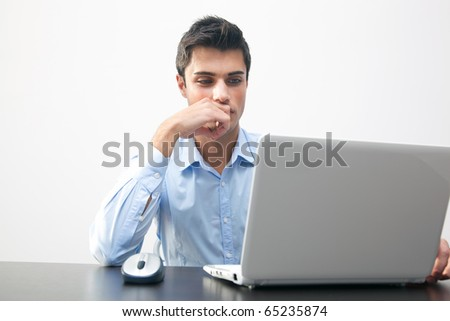 Thoughtful young businessman at work at his laptop