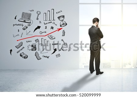 Thoughtful young businessman in concrete room with creative business sketch. Research concept