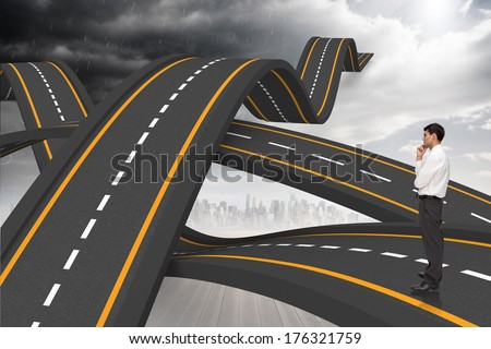 Thoughtful young businessman looking away against bumpy roads crossing backdrop - stock photo