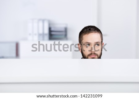 Thoughtful young businessman looking away in office cubicle - stock photo