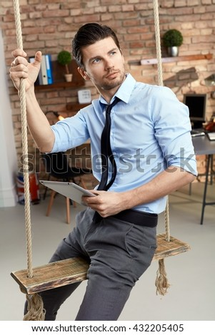 Thoughtful young businessman sitting in swing in modern office, holding tablet computer. - stock photo