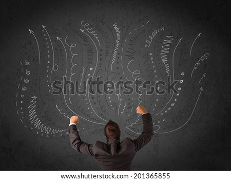 Thoughtful young businessman standing and deciding in front of a chalkboard with sketched arrows and lines in different directions - stock photo