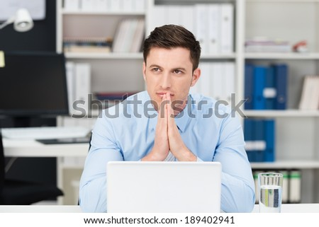 Thoughtful young businessman trying to solve a business problem sitting at his desk with his hands steepled as he stares into the distance in contemplation - stock photo