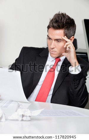 Thoughtful young businessman working at desk in office - stock photo