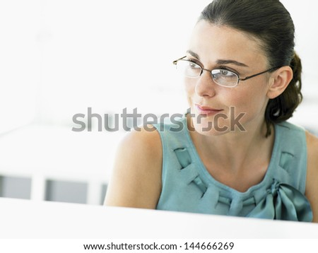 Thoughtful young businesswoman looking away in office - stock photo