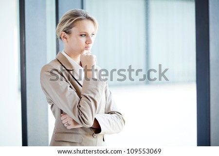 thoughtful young businesswoman looking outside of window - stock photo