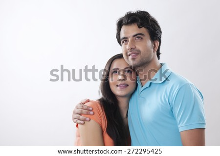 Thoughtful young couple smiling against white background - stock photo