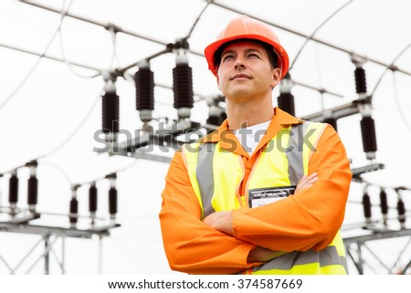 thoughtful young engineer looking away in substation