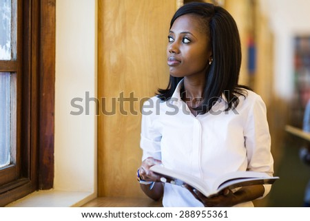 thoughtful young female african college student in library - stock photo