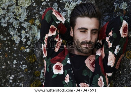 Thoughtful young hipster against rocks - stock photo