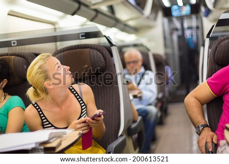 Thoughtful young lady surfing online on smartphone while traveling by train. - stock photo