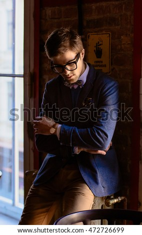 Thoughtful young man in black glasses leans to  the wall while standing in the restaurant