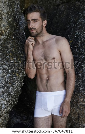 Thoughtful young man in underpants standing by rocks - stock photo