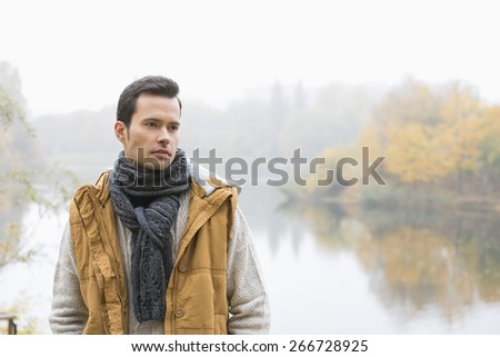 Thoughtful young man in warm clothing standing against lake - stock photo