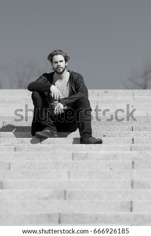 thoughtful young man sitting on a flight of steps staring into the distance with a serious expression against a blue sky background, black and white