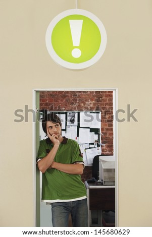 Thoughtful young man standing in doorway with sign of exclamation mark above in office - stock photo