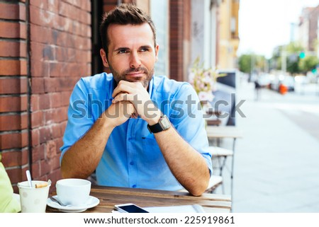 Thoughtful young man waiting in outdoor cafe - stock photo