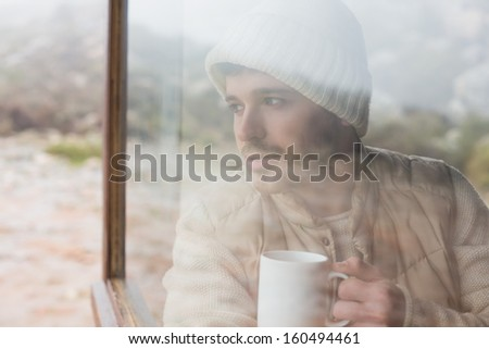 Thoughtful young man with coffee cup looking out through cabin window - stock photo