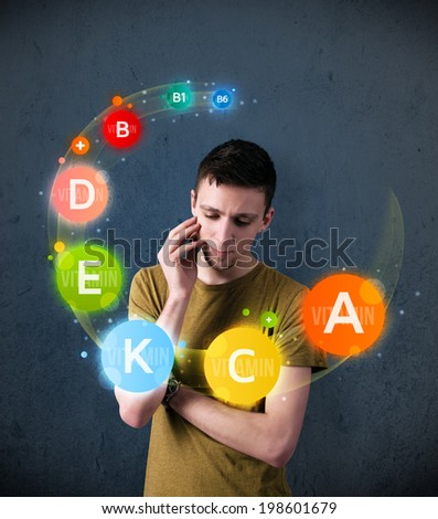 Thoughtful young man with vitamin icons circulating around his head - stock photo
