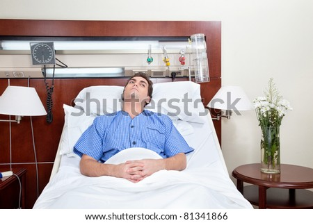 Thoughtful young patient lying on bed in hospital - stock photo