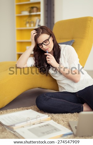 Thoughtful Young Pretty Woman Staring at her Workbook on the Floor While Leaning on the Chair and Putting her Pen on her Lips. - stock photo