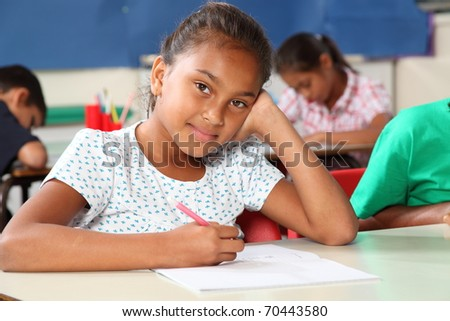 Thoughtful young schoolgirl in classroom writing - stock photo