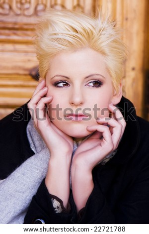 Thoughtful young short haired blond woman - stock photo