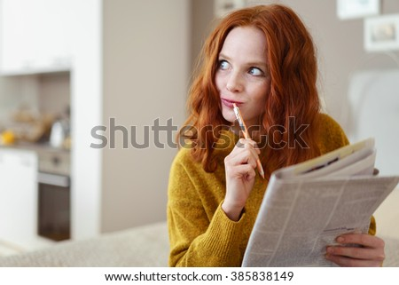 Thoughtful young woman doing a cryptic crossword puzzle in a newspaper looking off to the side with a pensive expression as she tries to solve a clue - stock photo