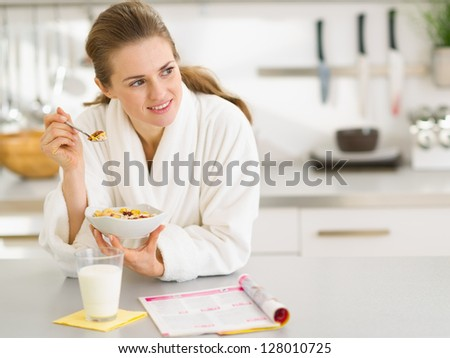 Thoughtful young woman in bathrobe eating breakfast in kitchen - stock photo