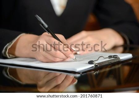 Thoughtful young woman in formalwear examining a document while sitting at the restaurant