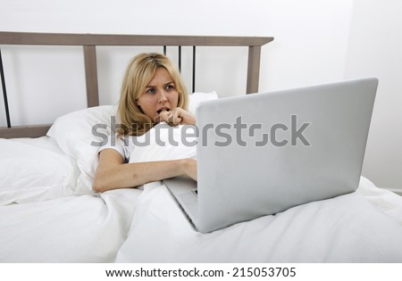Thoughtful young woman looking at laptop in bed - stock photo