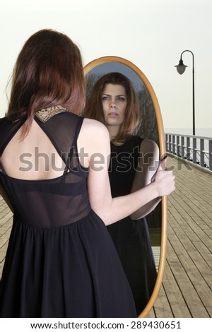 thoughtful young woman looks at the reflection in the mirror - solitude lonely concept - stock photo