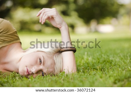 Thoughtful young woman resting in the park - stock photo