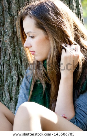 Thoughtful young woman seating near the tree. - stock photo