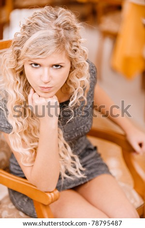 Thoughtful young woman sits in beautiful armchair and smiles, against magnificent interior.