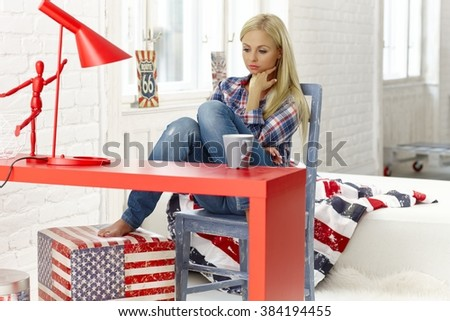 Thoughtful young woman sitting at desk at home in bad mood, looking down, - stock photo
