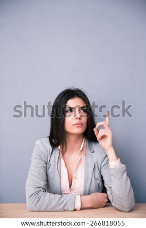 Thoughtful young woman sitting at the table and pointing up over gray background. Looking up at copyspace - stock photo