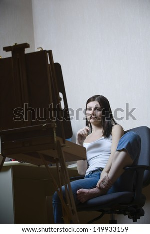 Thoughtful young woman sitting in front of easel at home
