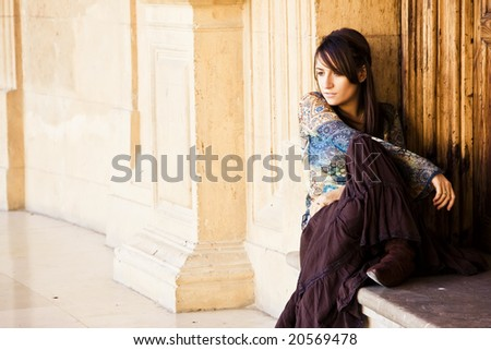 Thoughtful young woman sitting in old building.