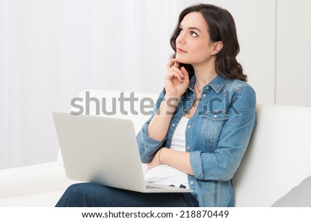 Thoughtful Young Woman Sitting On Couch With Laptop - stock photo