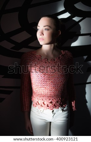 Thoughtful young woman wearing knitted sweater posing near wall - stock photo