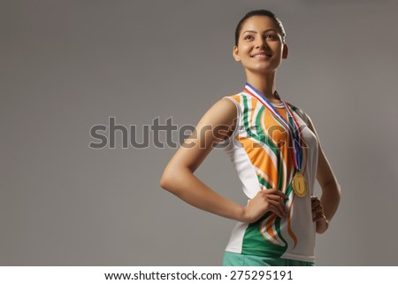 Thoughtful young woman wearing medal with hands on hip isolated over gray background - stock photo