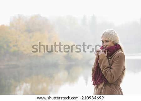 Thoughtful young woman wearing muffler at lakeside in park - stock photo