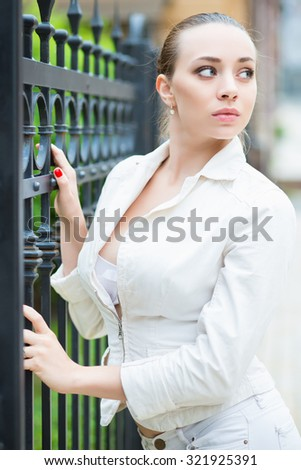 Thoughtful young woman wearing white jacket posing near metal fence - stock photo