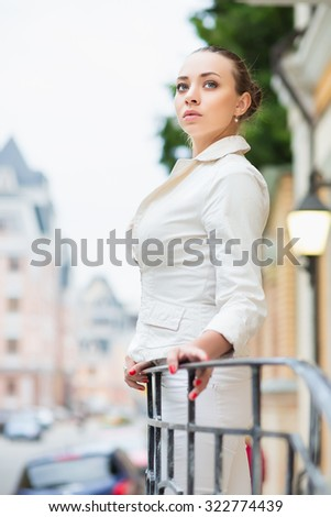 Thoughtful young woman wearing white jacket posing outdoors - stock photo