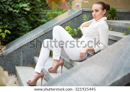 Thoughtful young woman wearing white pants and jacket posing on the stairs - stock photo