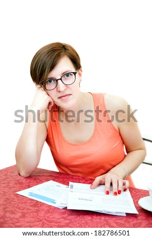 thoughtful young woman with bills - stock photo