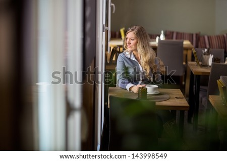 Thoughtful young woman with coffee cup sitting at table at cafe - stock photo