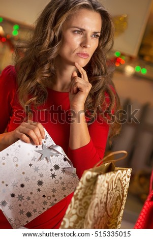 Thoughtful young woman with shopping bags in christmas decorated kitchen